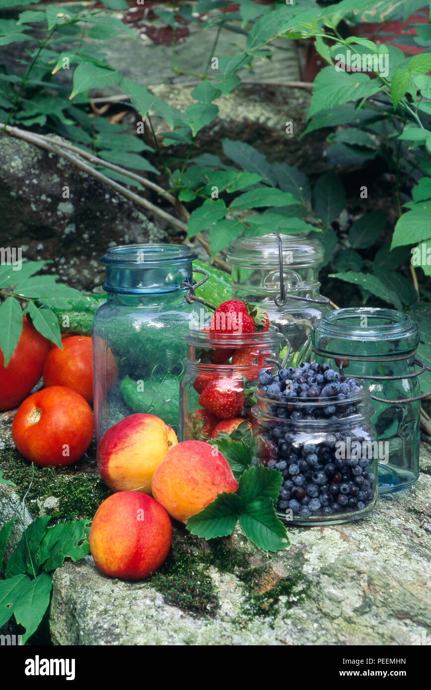 Fresh fruit, berries and tomatoes with old-fashioned home preserving jars. Photograph - Stock Image