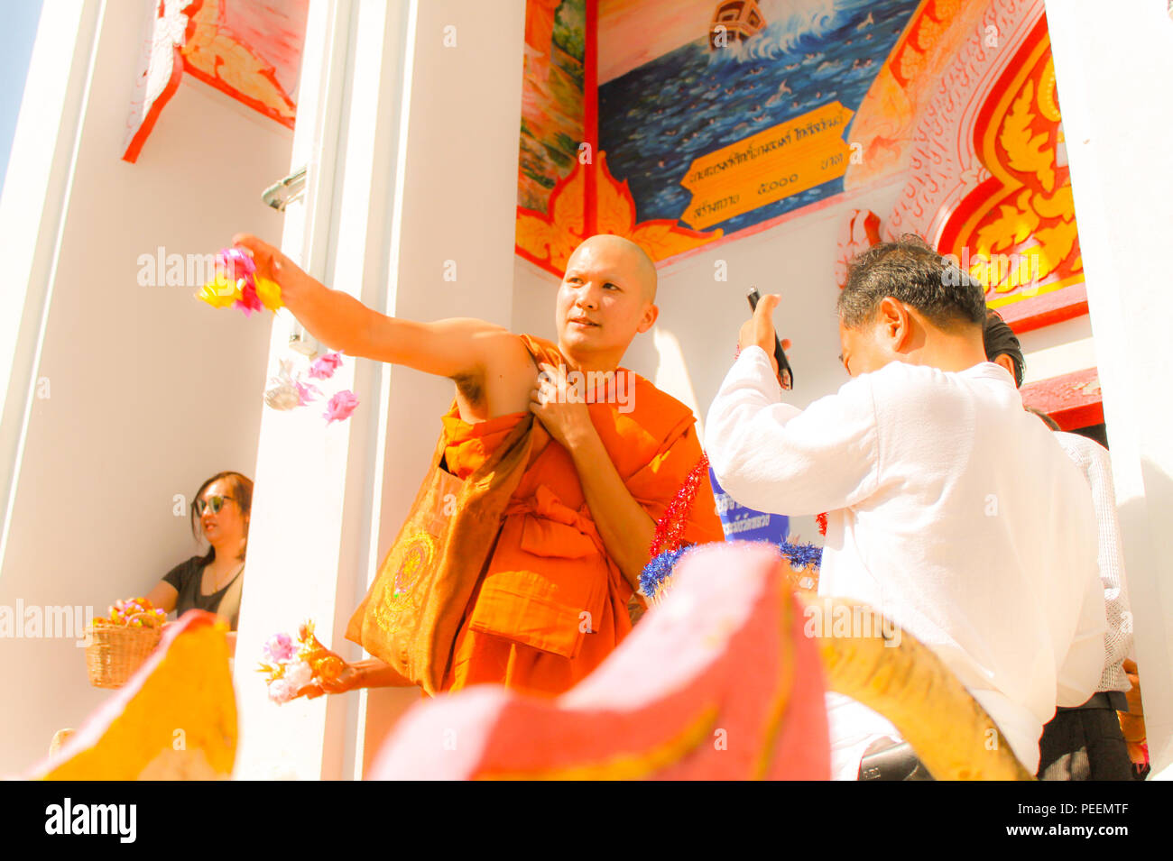Ubon ratchathani, Thailand - Rookie monk and his relatives scattering donate alms flowers (wrapped money) at Thai temple. - Stock Image