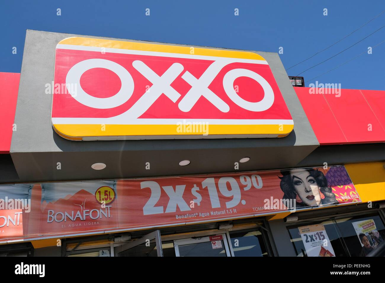 Oxxo convenience store in Mexico with a banner using the image of Mexican film star Maria Felix to advertise the sale of Bonafont bottled water. - Stock Image