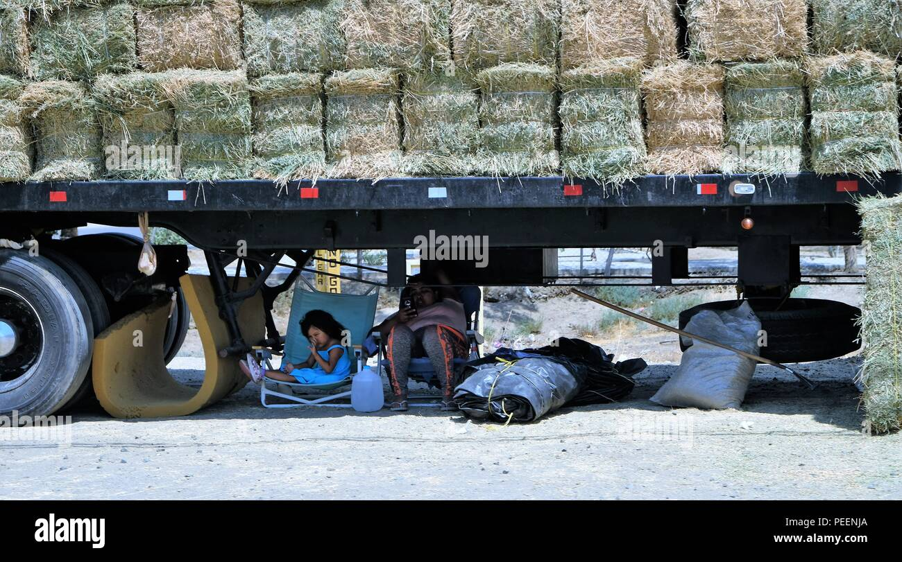 Mother and daughter sitting under a semi truck bed carrying bales of hay on the side of the road in Tecate, Baja California, Mexico. - Stock Image