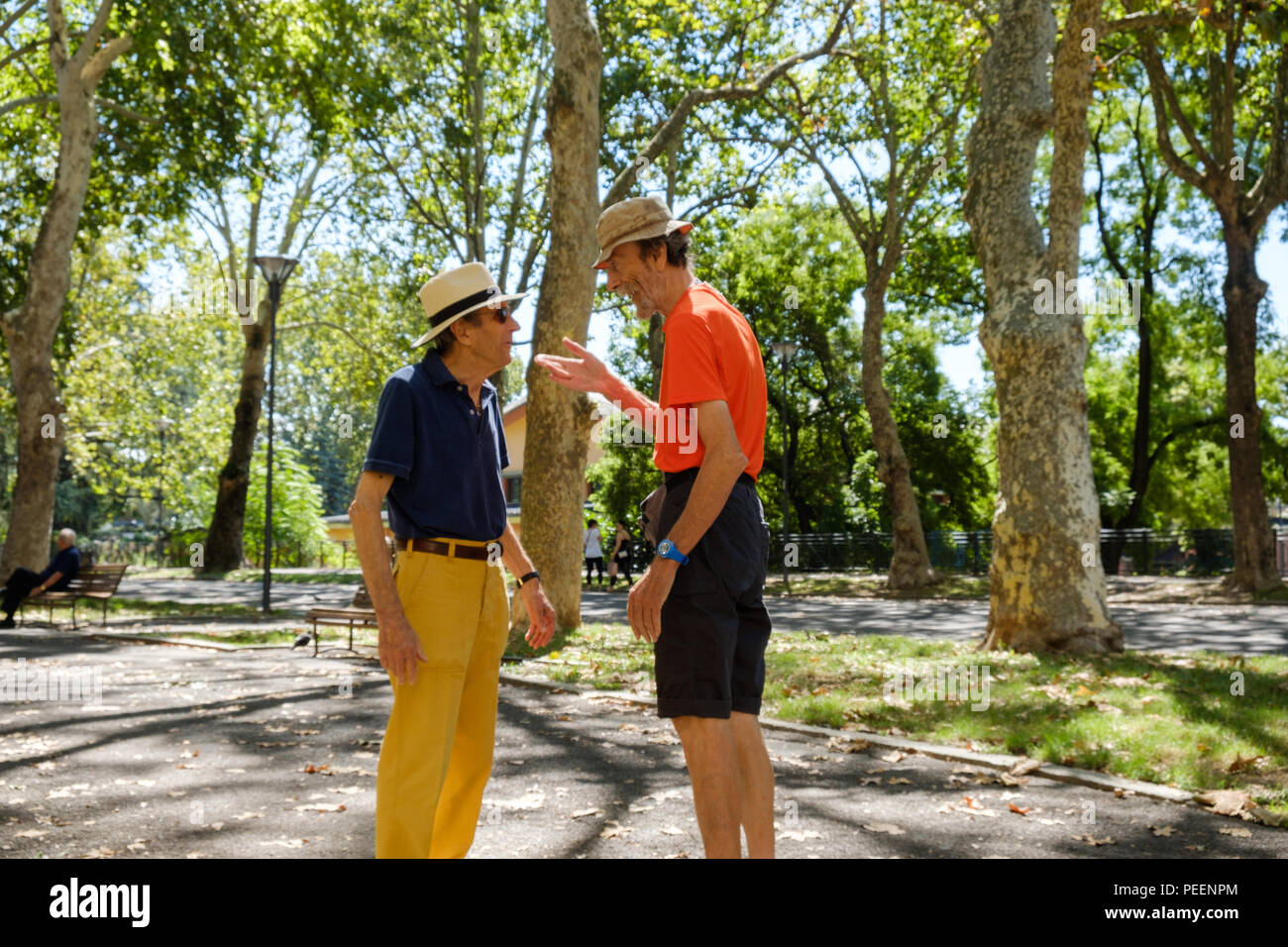 Colourfully dressed italian men both with straw hats meeting and greeting each other on a summers morning at the park. Piacenza, Italy. Stock Photo