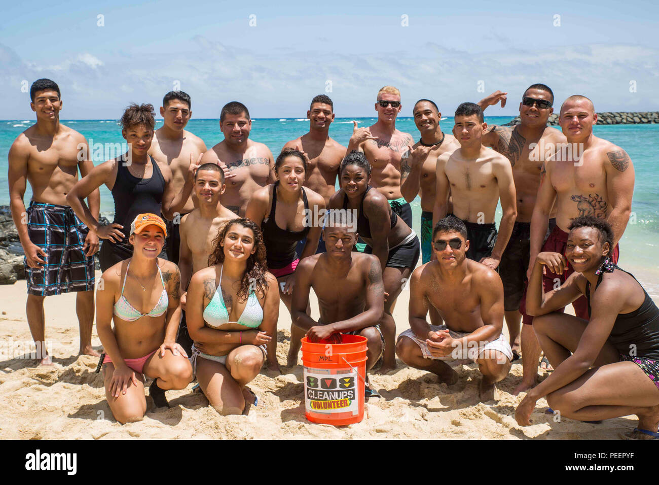 Marines and Sailors pose for a photo after volunteering with non-profit organization, 808 Cleanups, at the Makai Research Pier August 8, 2015. The service members collected 136 pounds of marine debris that was comprised of things such as fishing line, metal, plastic and glass from the waters surrounding the pier and on the beach. Participating in event such as this, give service members the opportunity to give back to the local community. (U.S. Marine Corps photo by Cpl. Brittney Vito/Released) - Stock Image