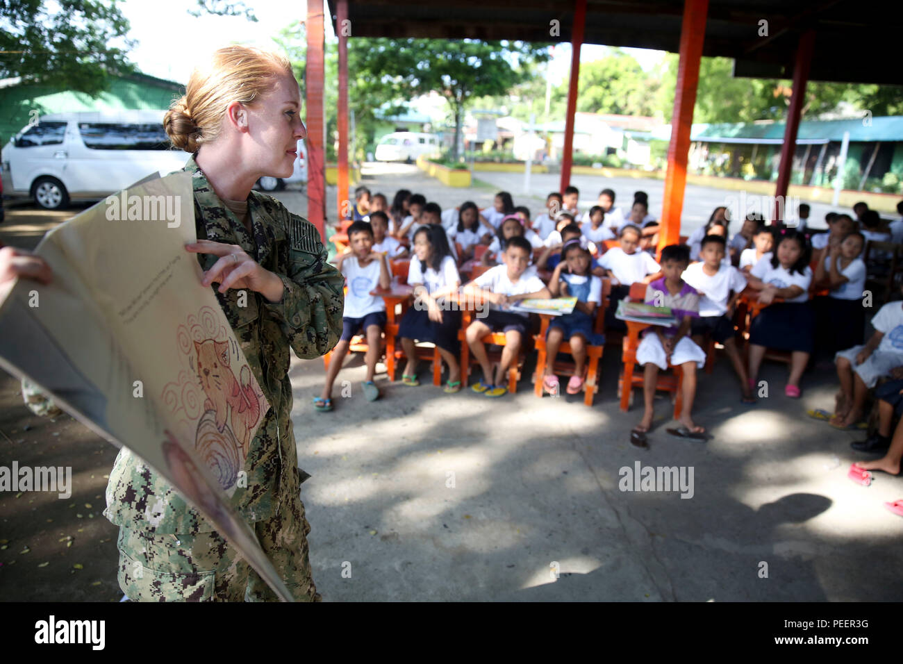 150812-M-GO800-041 SAN FERNANDO CITY, Philippines (Aug. 12, 2015) – Lt. j.g. Elizabeth Gerardo reads to students at Pagudpud Elementary School Aug. 12. Task Force Forager will be in the Philippines until Aug. 15 providing medical and engineering assistance. Task Force Forager, embarked aboard the Military Sealift Command joint high speed vessel USNS Millinocket (JHSV 3) is serving as the secondary platform for Pacific Partnership, led by an expeditionary command element from the Navy's 30th Naval Construction Regiment (30 NCR) from Port Hueneme, Calif. Now in its 10th iteration, Pacific Partne - Stock Image