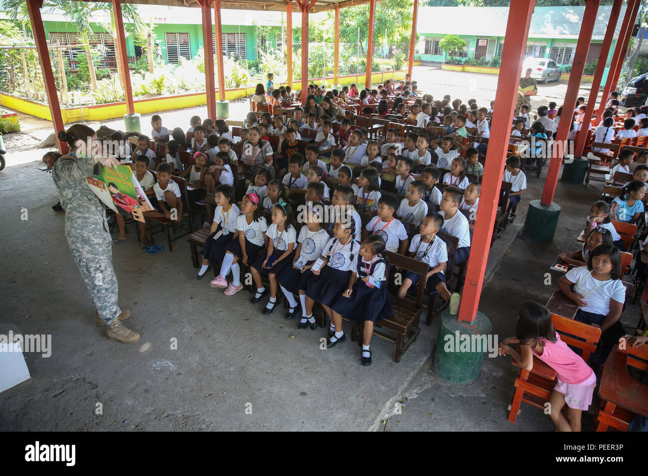 150812-M-GO800-051 SAN FERNANDO CITY, Philippines (Aug. 12, 2015) – U.S. Army Capt. Desiree Giangregorio reads to students at Pagudpud Elementary School Aug. 12. Task Force Forager will be in the Philippines until Aug. 15 providing medical and engineering assistance. Task Force Forager, embarked aboard the Military Sealift Command joint high speed vessel USNS Millinocket (JHSV 3) is serving as the secondary platform for Pacific Partnership, led by an expeditionary command element from the Navy's 30th Naval Construction Regiment (30 NCR) from Port Hueneme, Calif. Now in its 10th iteration, Paci - Stock Image