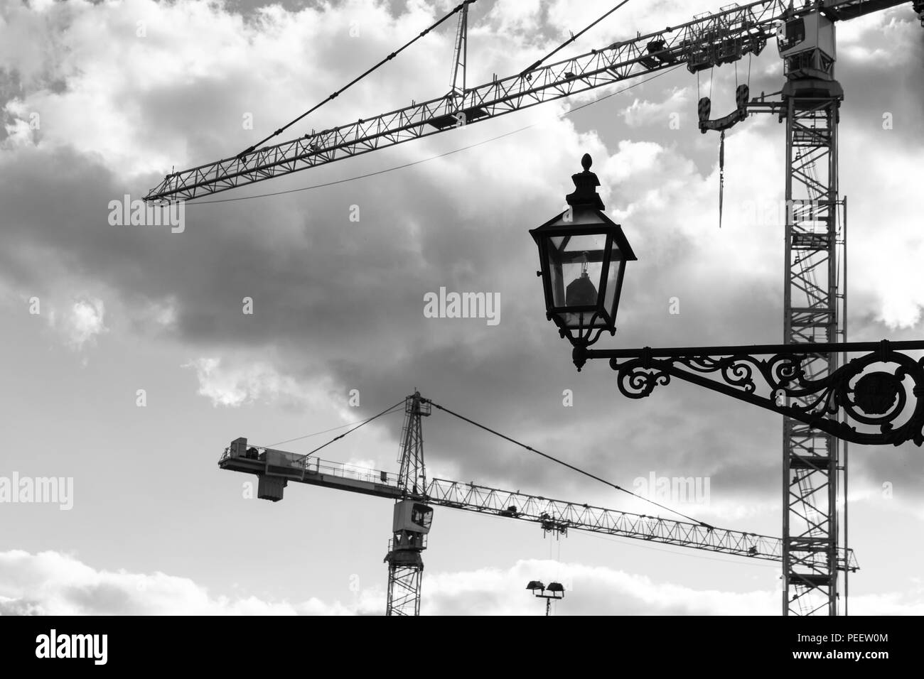 Tower cranes against the sky in the old town. BW - Stock Image