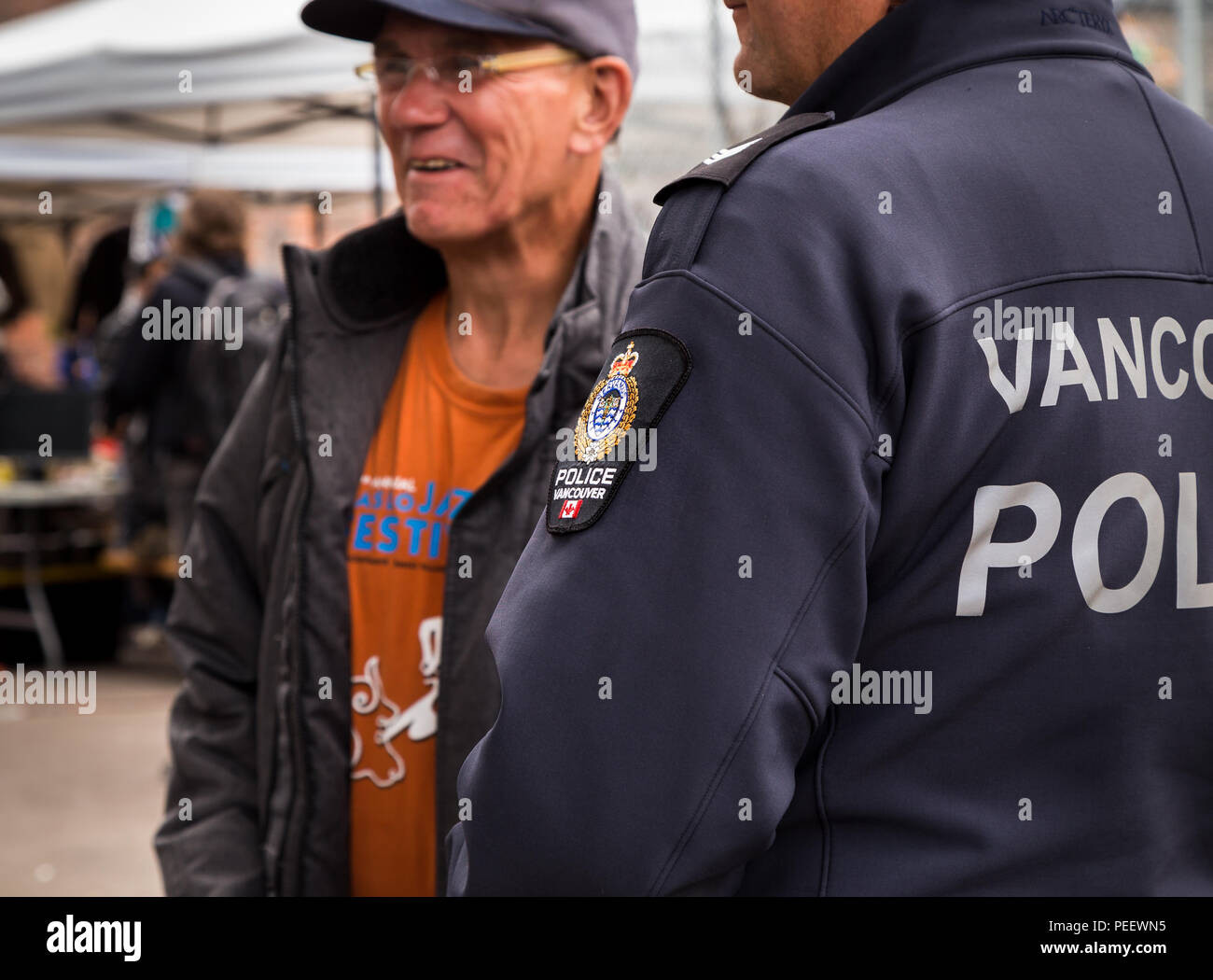 VANCOUVER, BC, CANADA - MAY 11, 2016: Vancouver police officer conversing with a member of the public. - Stock Image