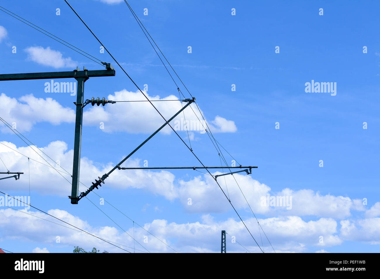 Electric train lines railway electrification overhead system with wires and blue sky above - Stock Image