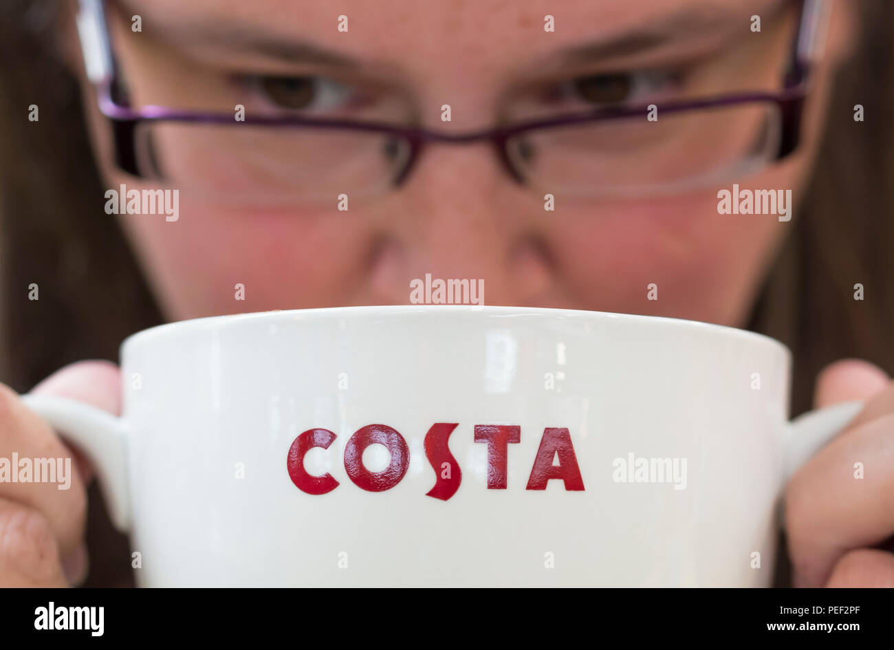 A woman drinking coffee from a large Costa Coffee mug with 2 handles, in the UK. - Stock Image