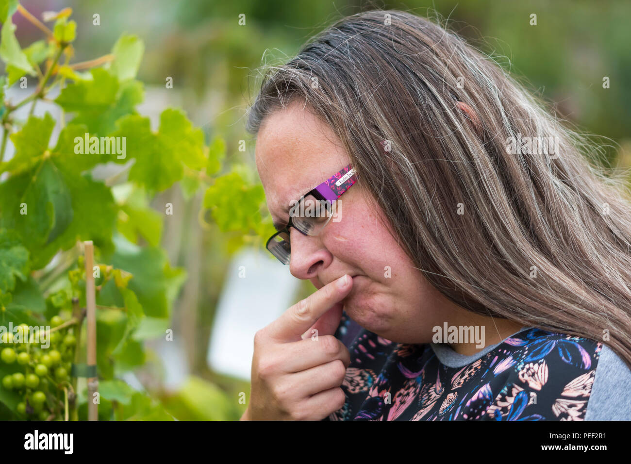 A woman making an inquisitive facial expression while trying to make a choice. Decision making concept. Trying to decide.Lots of options. - Stock Image