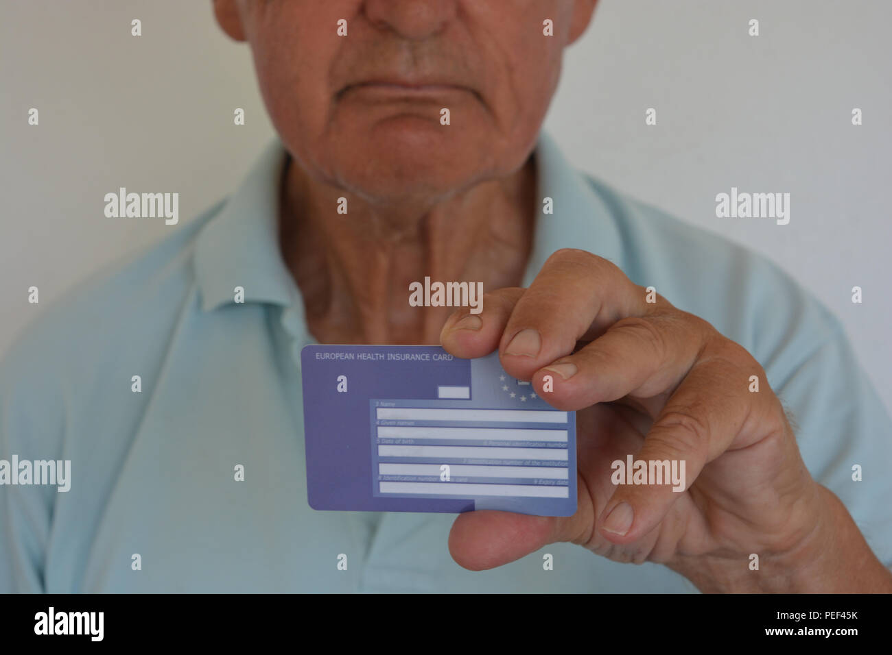 Man holding a European Health Insurance Card from the UK, selective focus on the card - Stock Image