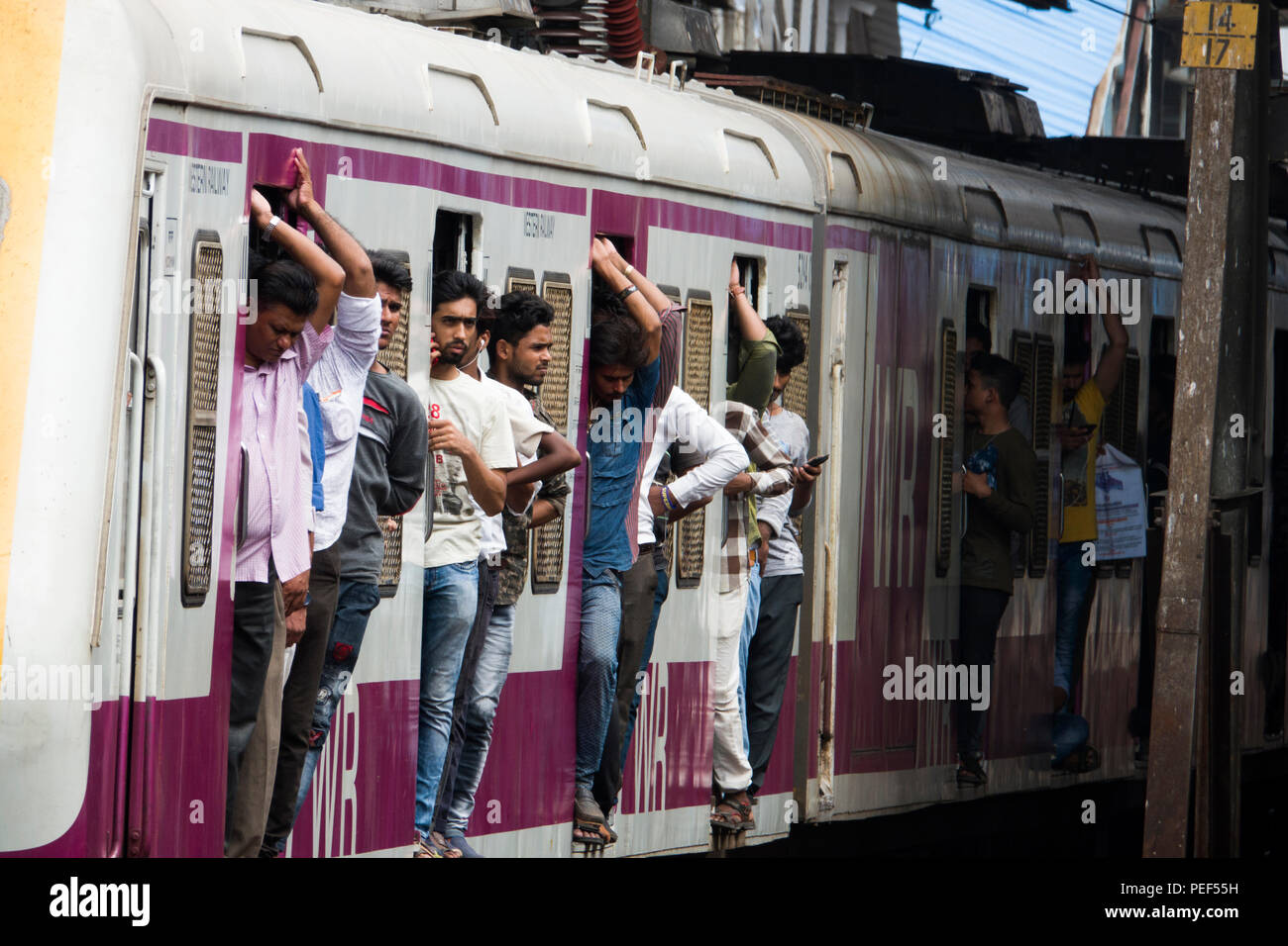 Passengers hanging out of trains door on a Mumbai Suburban Railway train at Bandra station in Mumbai, India - Stock Image