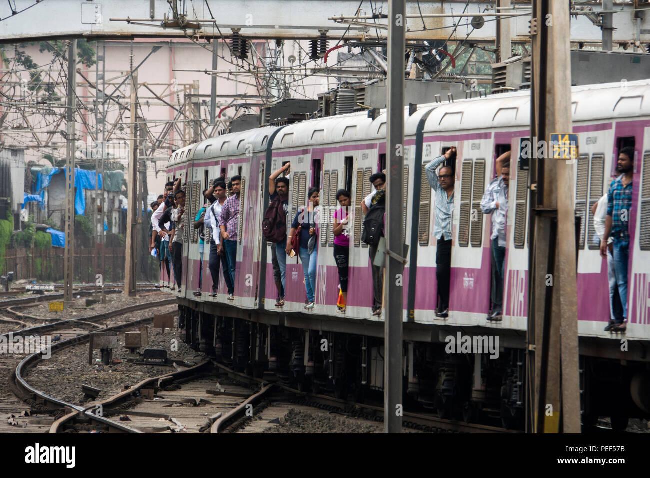 Passengers hanging out of trains door on a Mumbai Suburban Railway train arriving at Bandra station in Mumbai, India - Stock Image