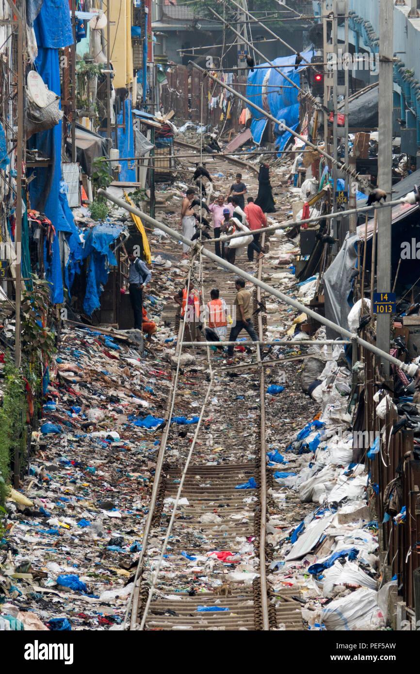 Piles of plastic trash next to train tracks and slum area at Bandra train station, Mumbai, India - Stock Image