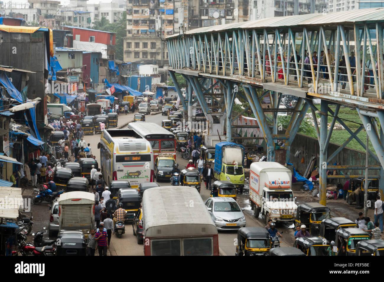 Busy traffic scene with Bandra skywalk pedestrian walkway above at Station road, Mumbai, India - Stock Image