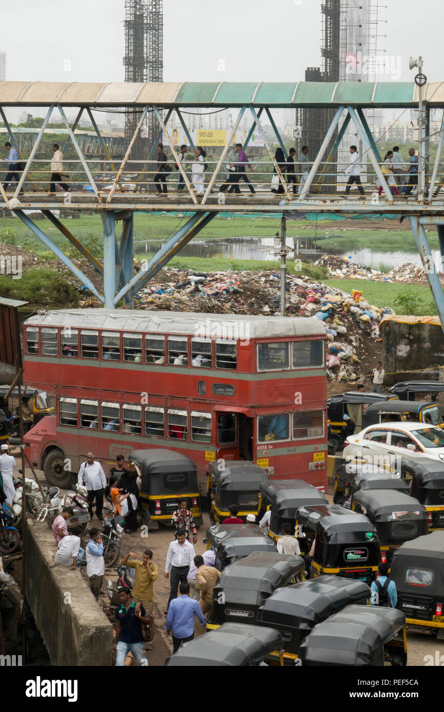 Double decker bus in traffic on Station road with Bandra pedestrian skywalk above, Mumbai, India - Stock Image