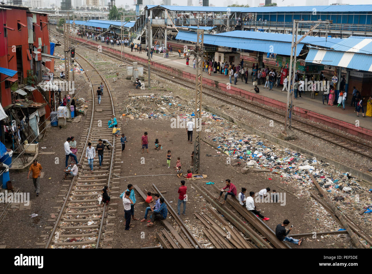 People from slum area with piles of plastic rubbish on tracks next to Bandra train station, Mumbai, Nepal - Stock Image