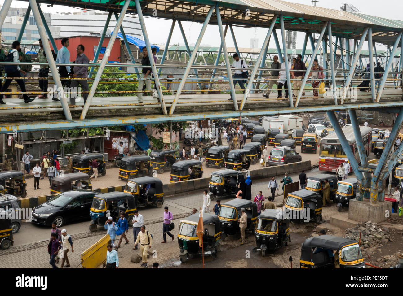 Auto rickshaw tuk tuks waiting for passengers at Bandra train station with skywalk pedestrian walkway above at Station road, Mumbai, India - Stock Image