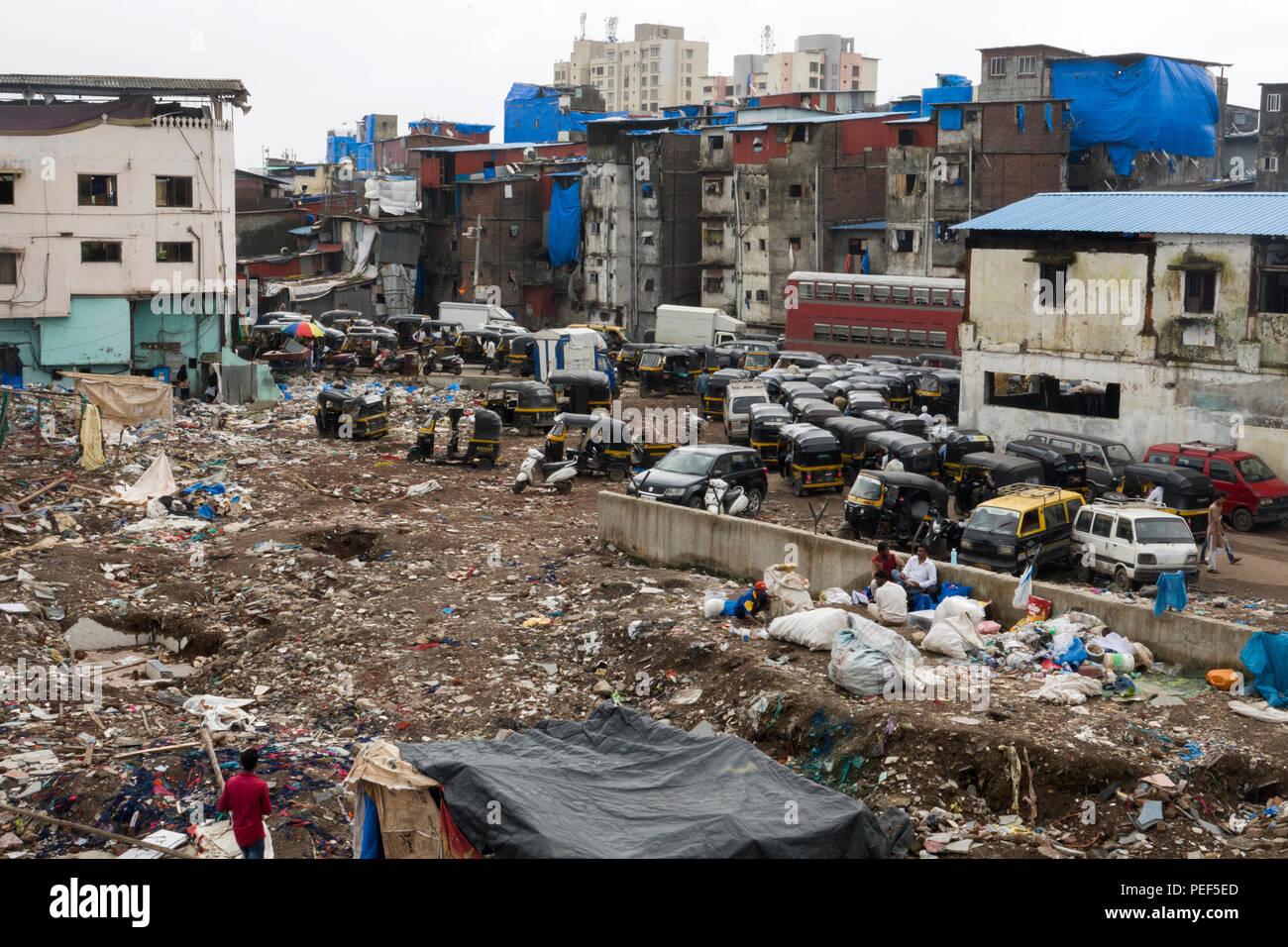 Slum area covered in trash with tuk tuk auto rickshaws waiting for passengers outside of Bandra railway station skywalk in Mumbai, India - Stock Image