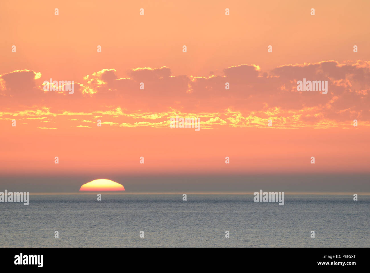 Sunset with clouds over the North Sea, sun sinks in the sea, Norderney, East Frisian Islands, Lower Saxony, Germany - Stock Image