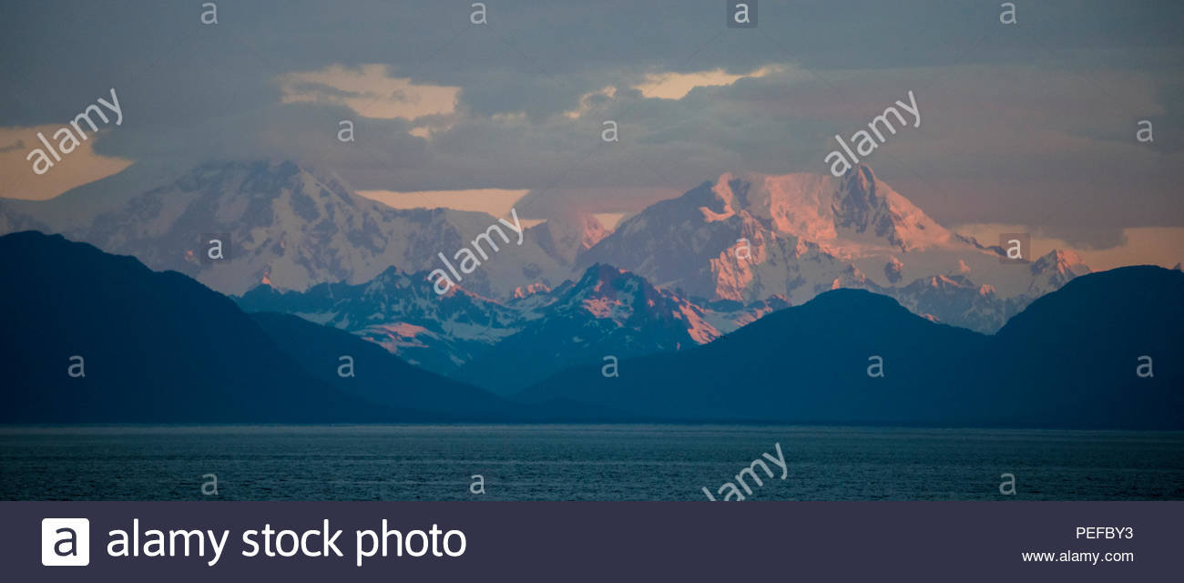 Sunrise looking north into Glacier Bay National Park, with the Fairweather range. - Stock Image