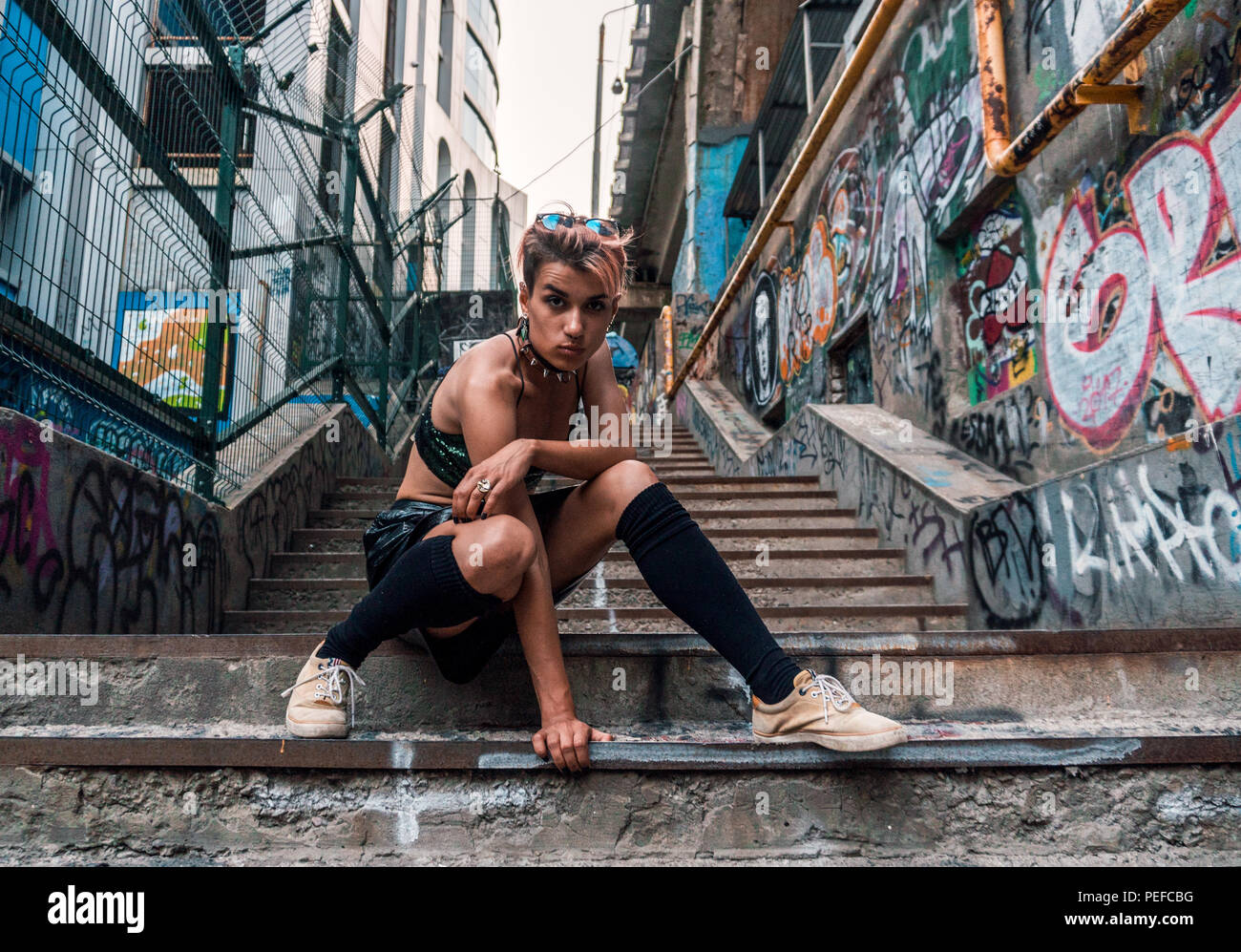Street Punk Girl Sitting On Concrete Stairs Urban Lifestyle In City Passage Painted With Graffiti Under The Bridge