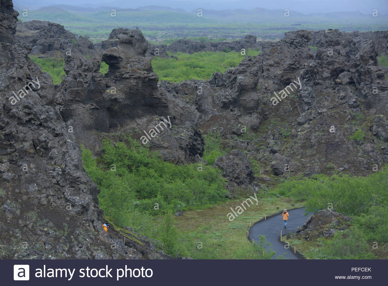 A hiker walks past the Dimmuborgir lava formations. Stock Photo