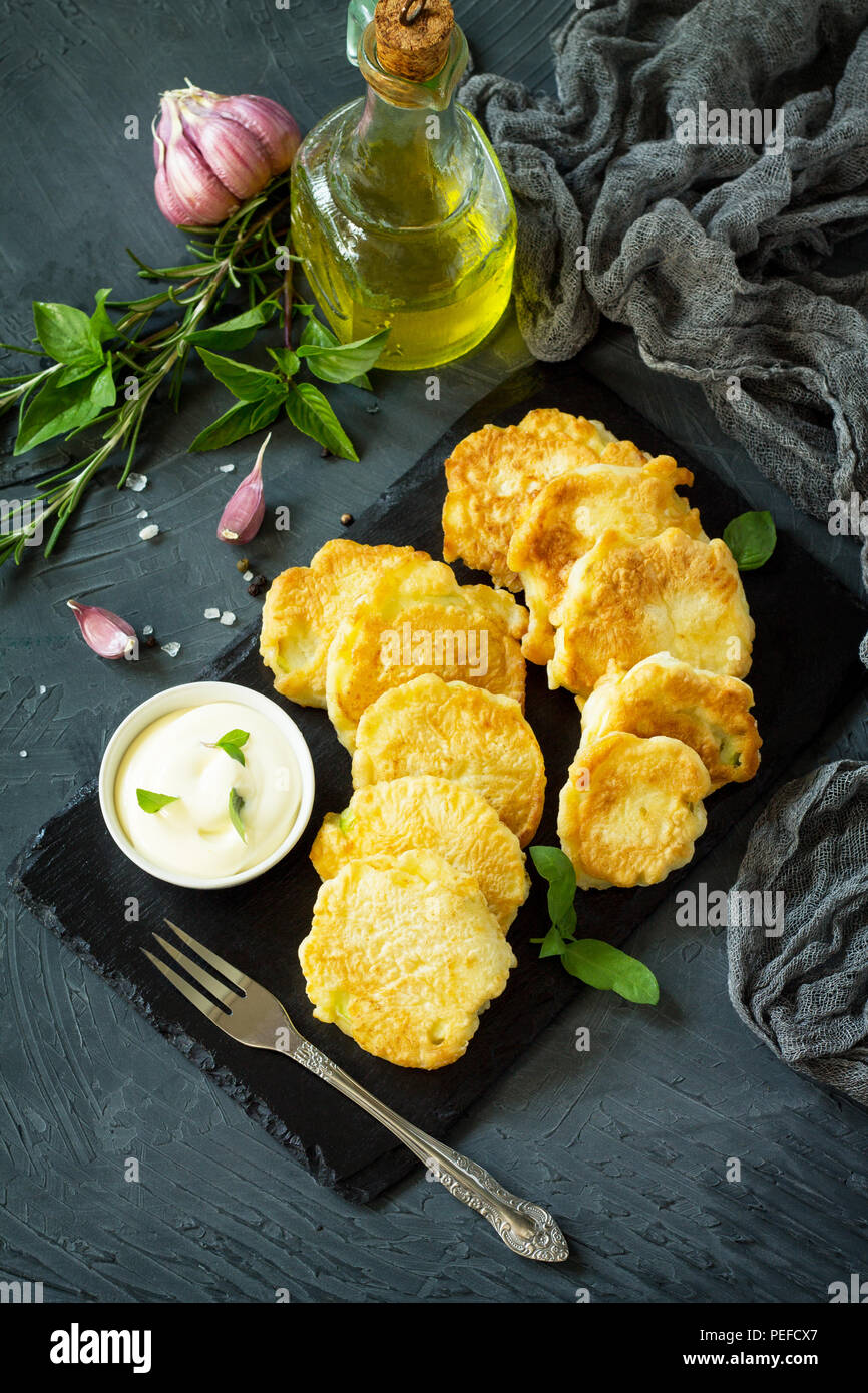 Vegan vegetable fritters on a background of slate cutting board. Fried vegetarian cutlets or pancakes. The concept of fast food. Copy space. Stock Photo
