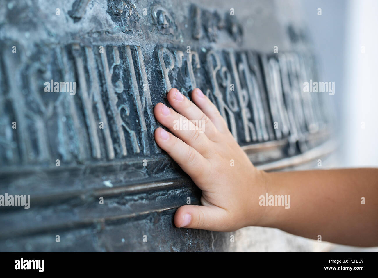 Close-up. The hand of the child touches a large church bell with ancient Slavic inscriptions. The concept of spirituality. Russia. Rostov the Great. - Stock Image
