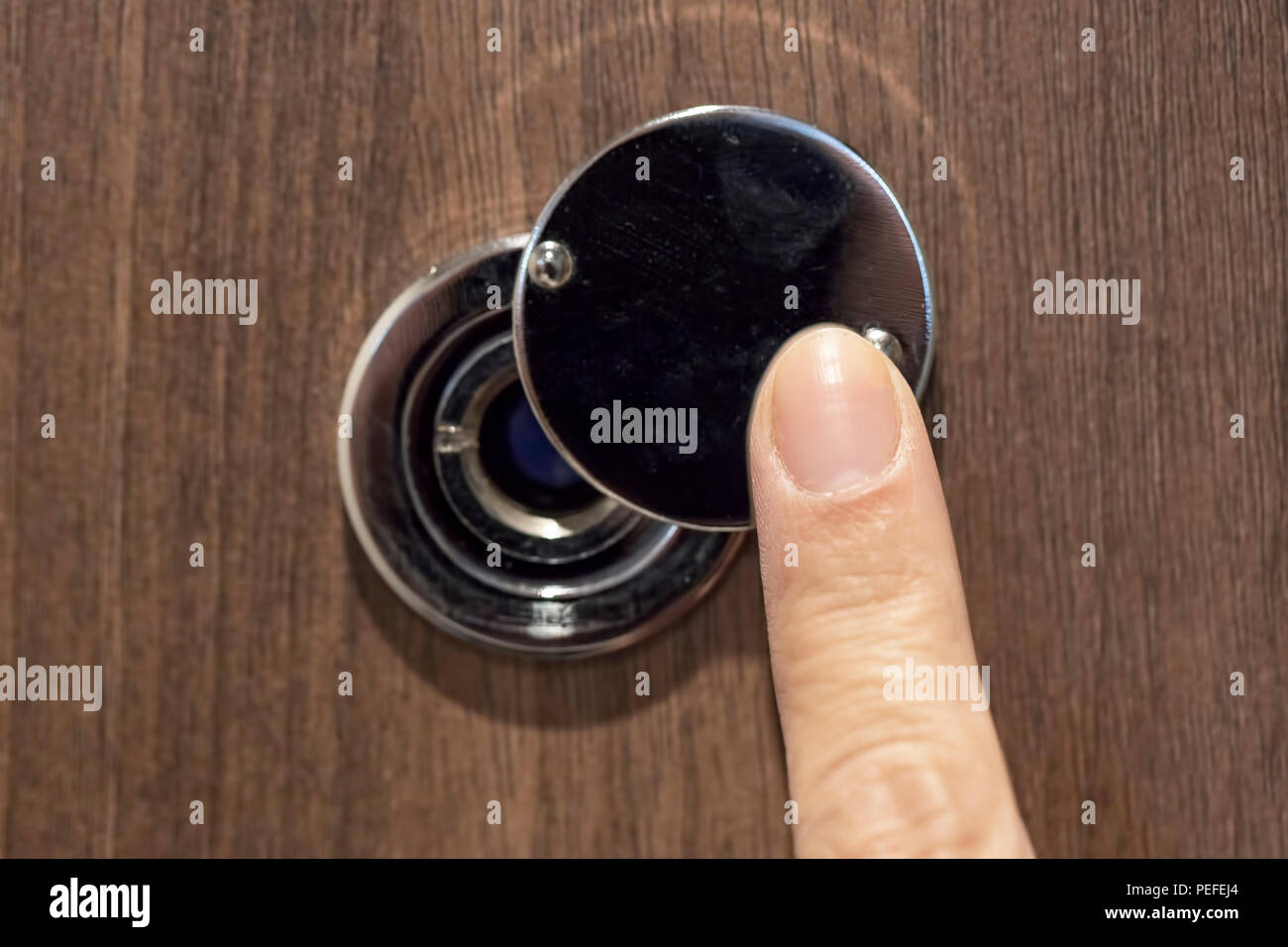 a female hand opens the cover door peephole - Stock Image