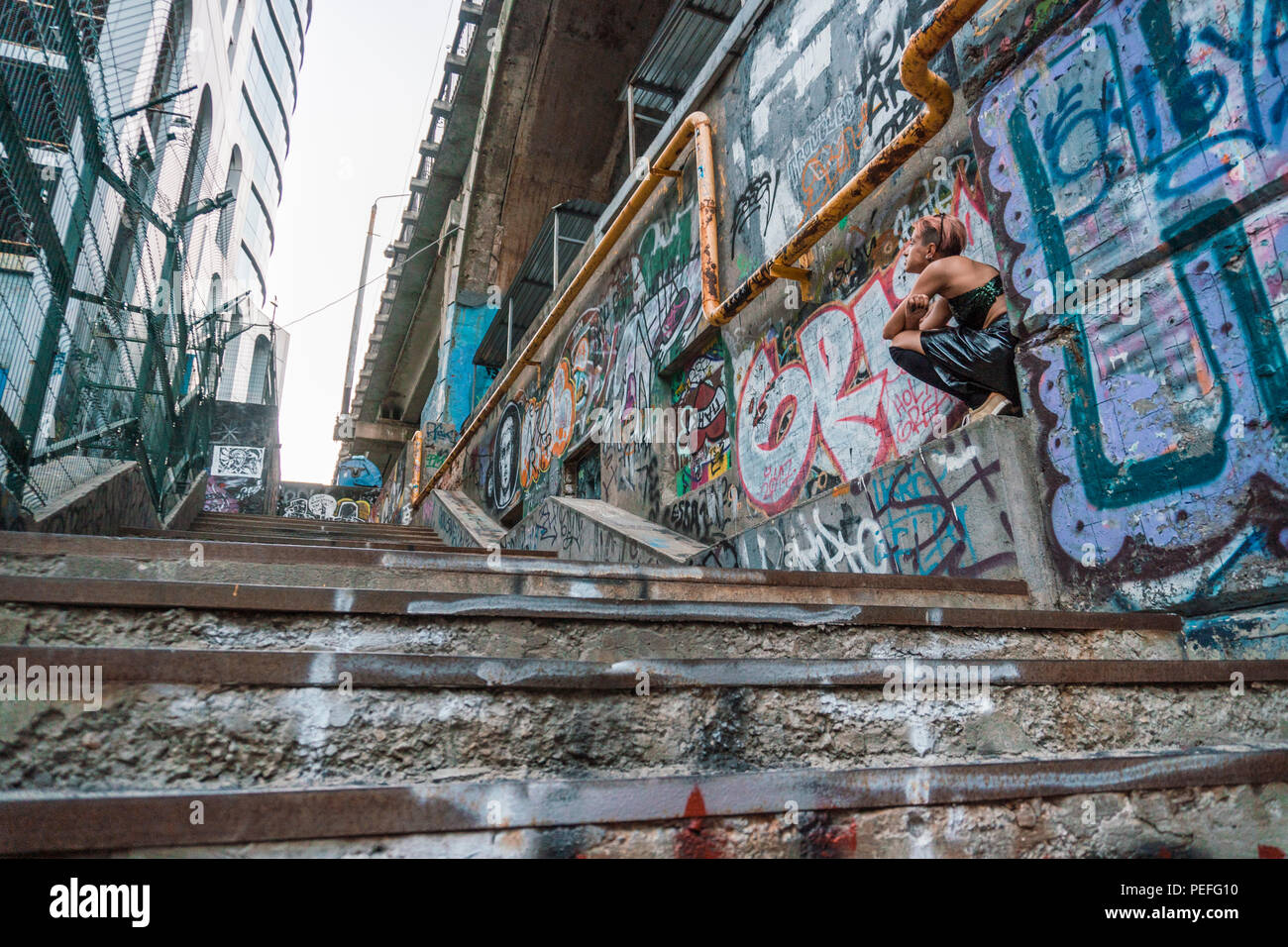 Wide Shot Of Street Punk Girl In Urban Girl Sitting On The Stairs Painted With Graffiti Under The Bridge