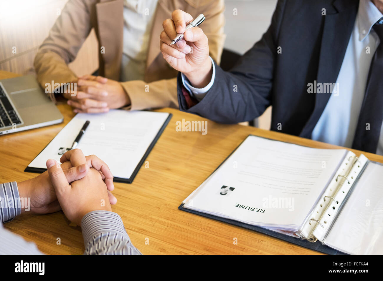 young man explaining about his profile to business managers sitting in job Interview. listen to candidate answers Hiring employee, nervously clutched  - Stock Image
