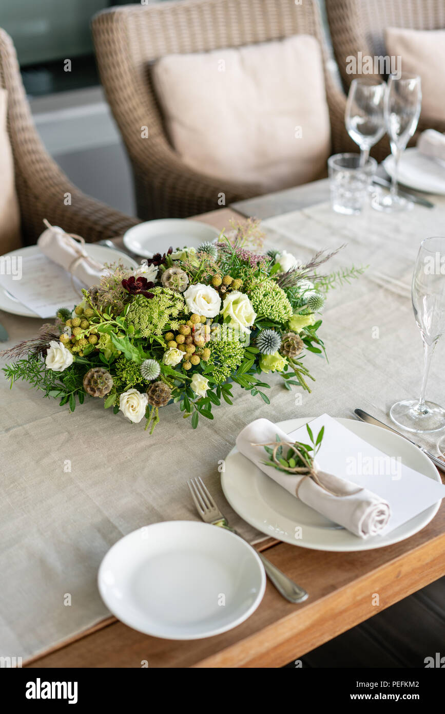 Wedding Banquet or gala dinner. The chairs and table for guests, served with cutlery and crockery. Covered with a linen tablecloth runner. party on terrace Stock Photo