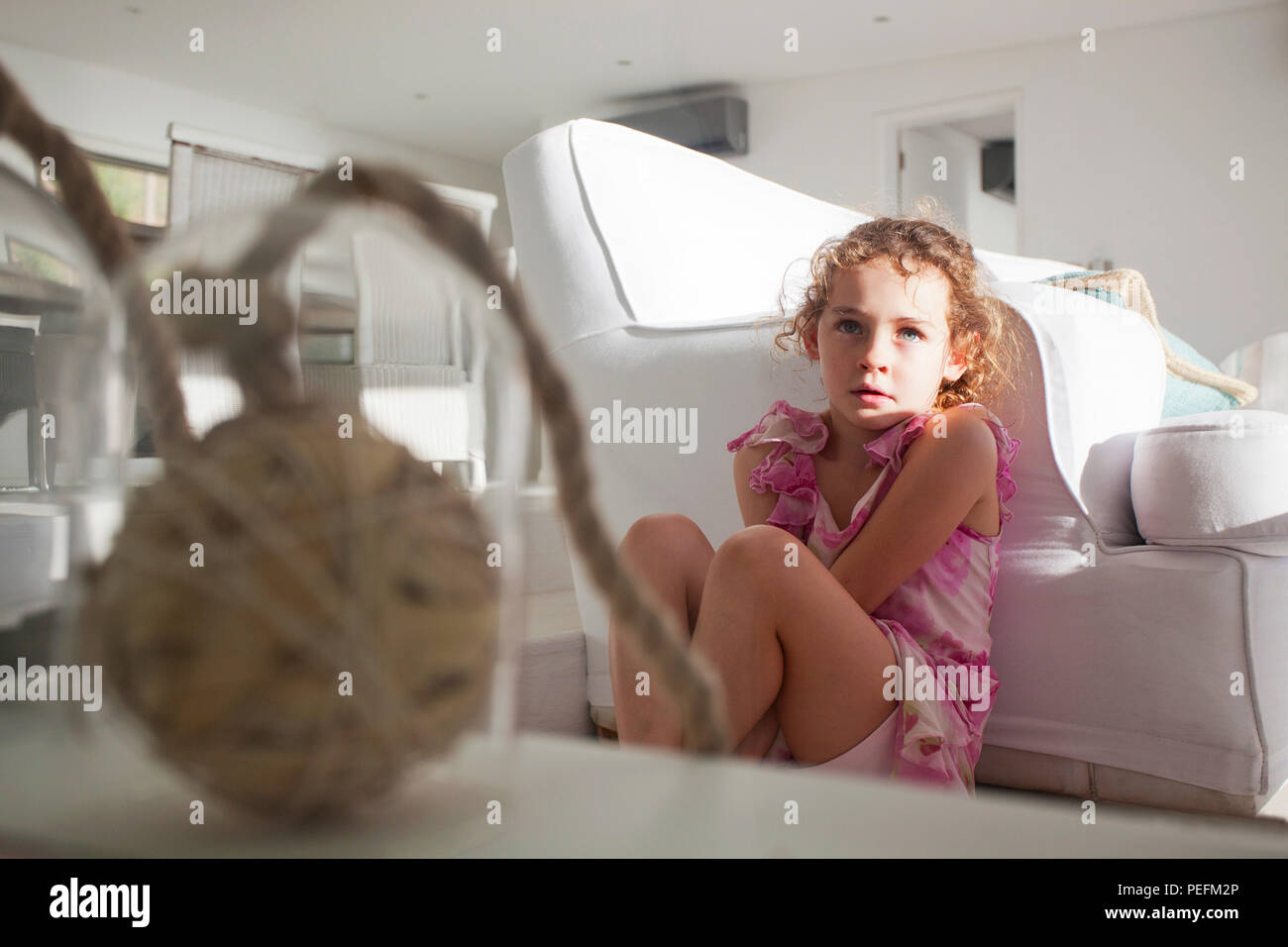 Young girl in pink seated - Stock Image