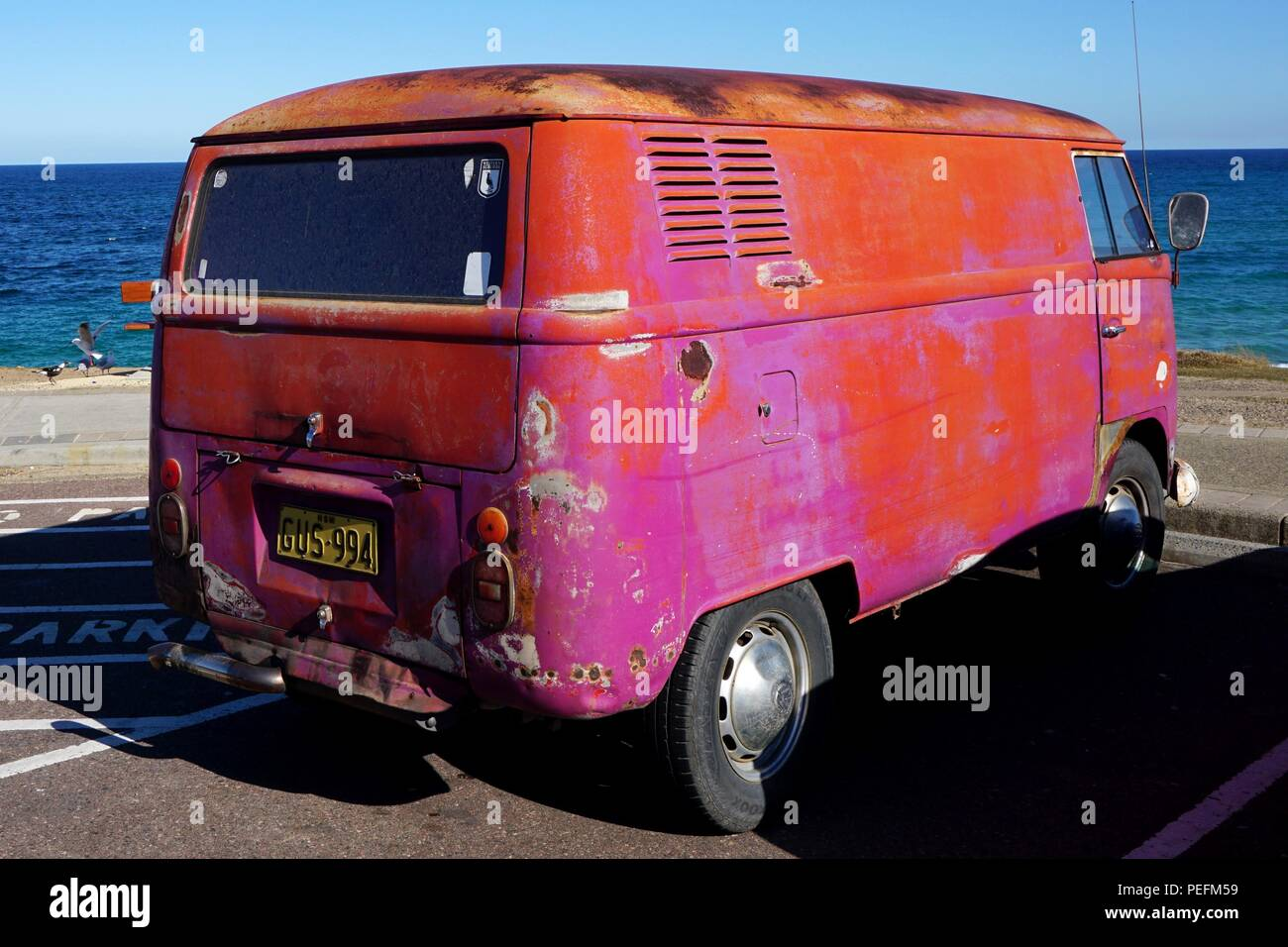 Close Up of Battered, Orange and Pink VW Campervan at Soldiers Beach, New South Wales, Australia - Stock Image
