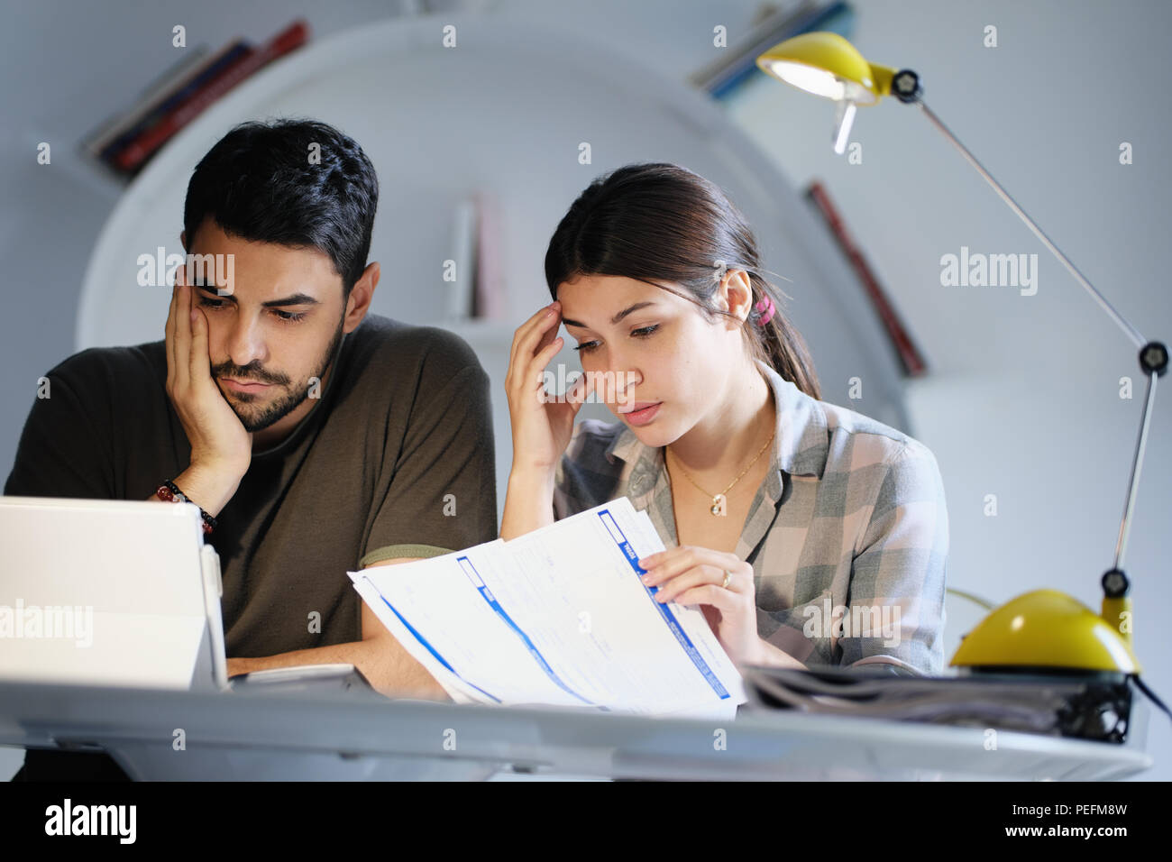 young couple reviewing invoices and doing family business plan