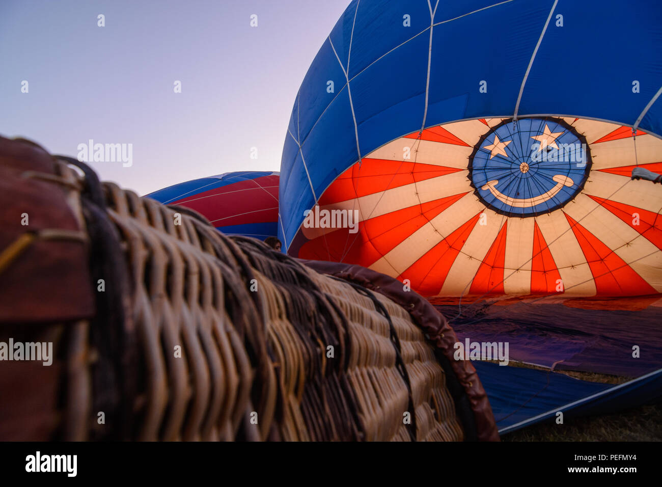 A hot air balloon and basket with a colorful smiley face being inflated just before the start of the Great Reno Balloon Race in 2017. - Stock Image