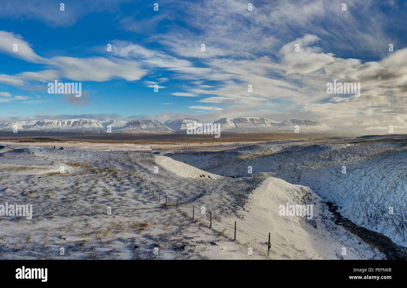 Winter Christmas landscape with trees and mountains. Christmas landscape on a sunny morning with blue sky and clouds and fresh snow. Photo taken in Ic - Stock Image