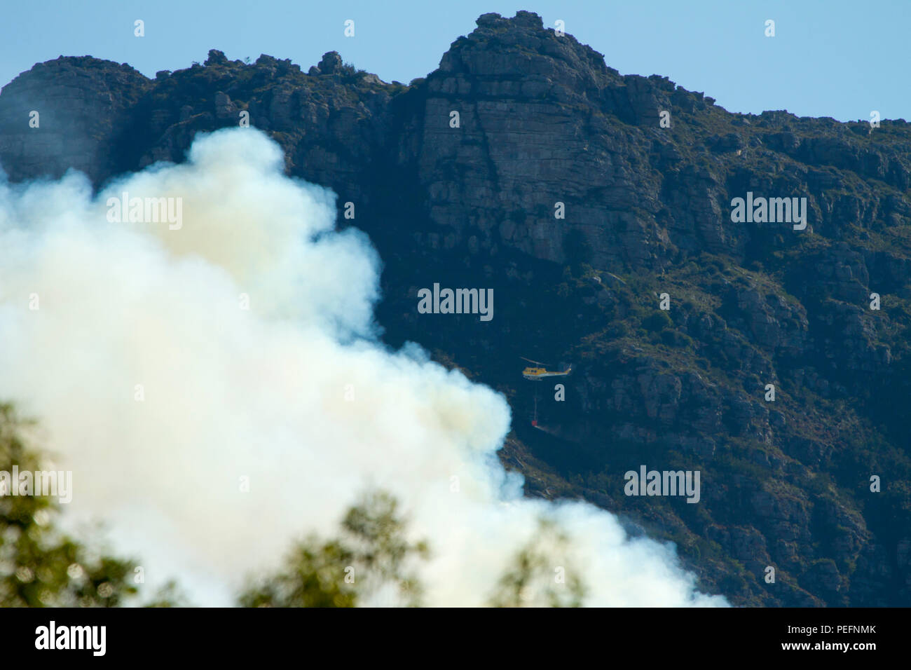 Firefighters tackle a forest fire on table mountain using helicopters - Stock Image