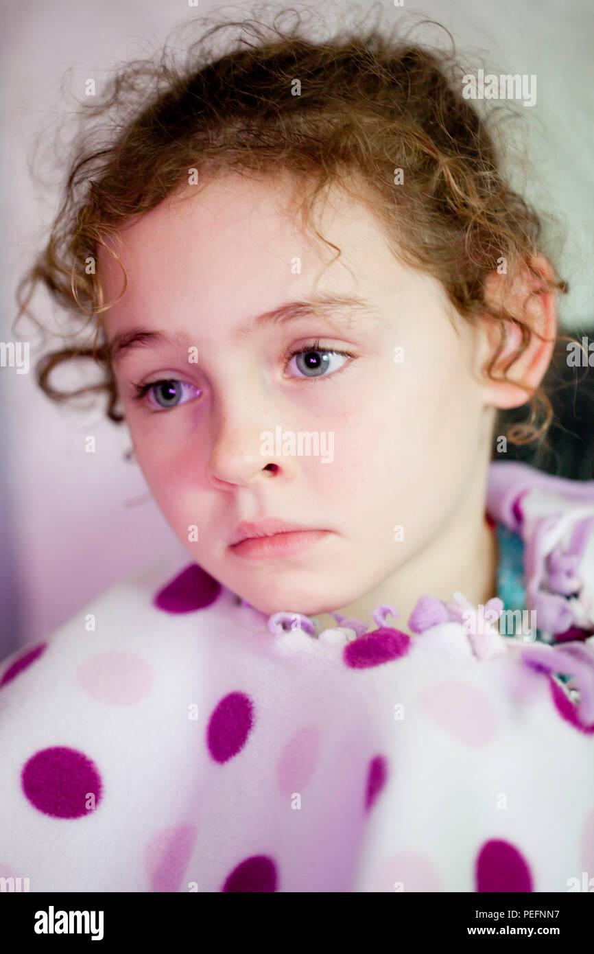 Portrait of a curly haired six year old girl deep in thought - Stock Image