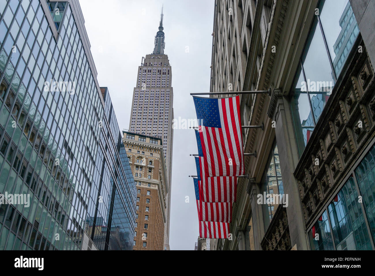 Empire State Building and American flags in New York City Stock Photo