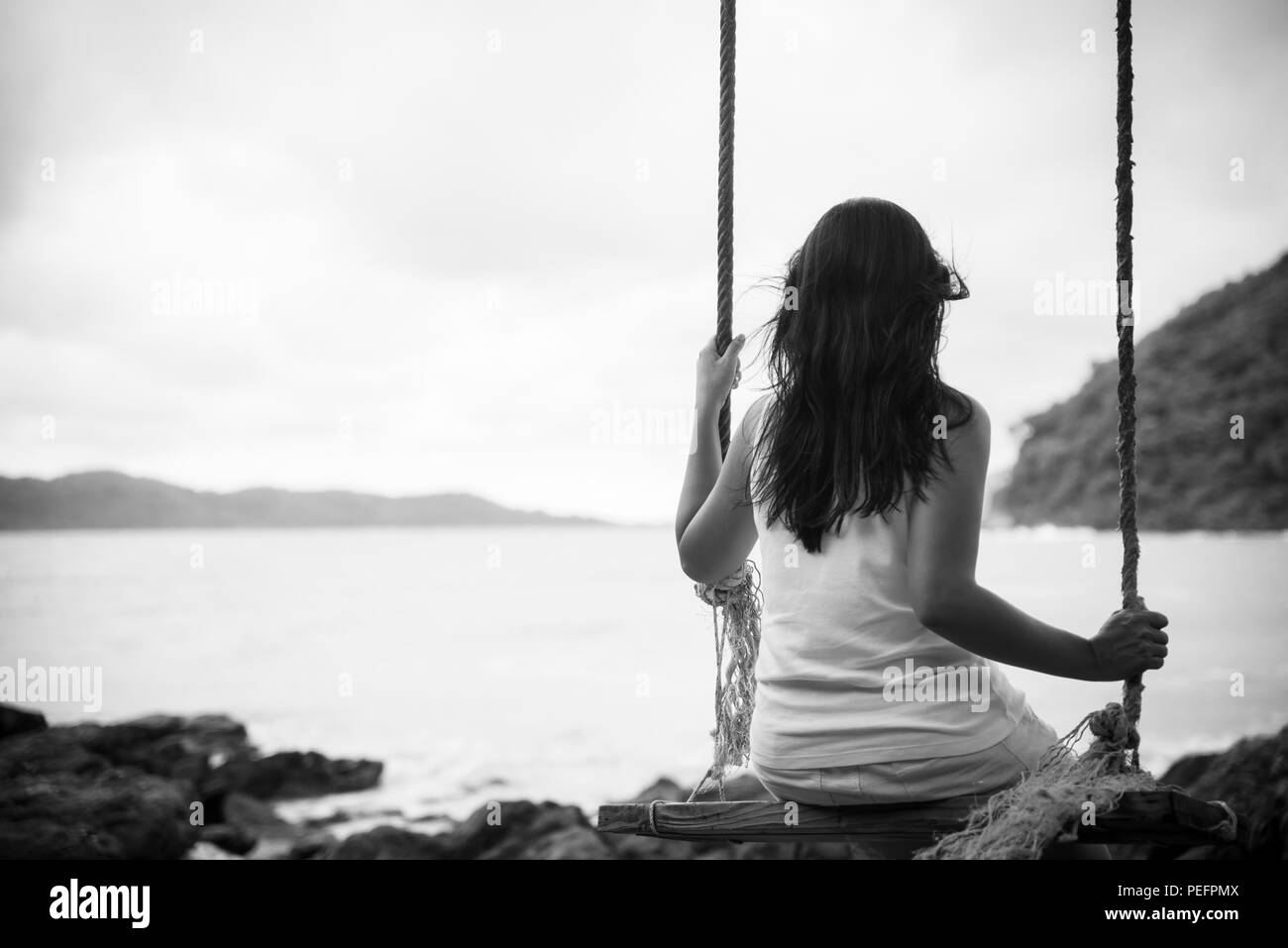 Black and white of sad and lonely woman sitting alone on a