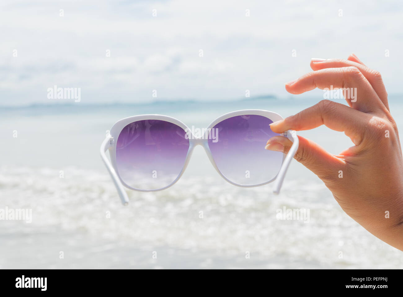 9f780f3bfbe woman hand holding sunglasses over sea and Sandy beach in background for  summer holiday and vacation concept.
