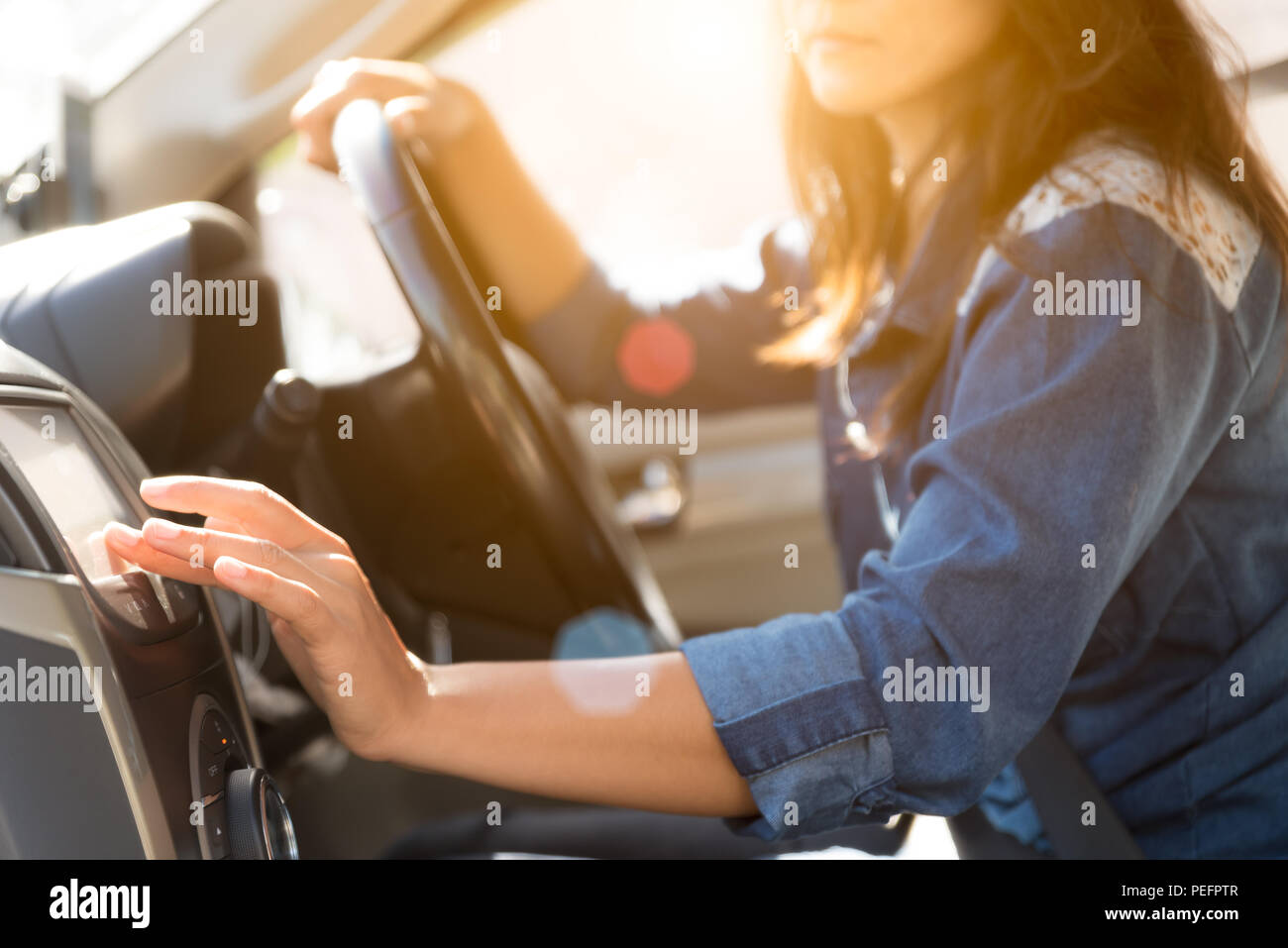 woman driver hand touching the screen entering an address into the navigation system and turning on car radio system. - Stock Image
