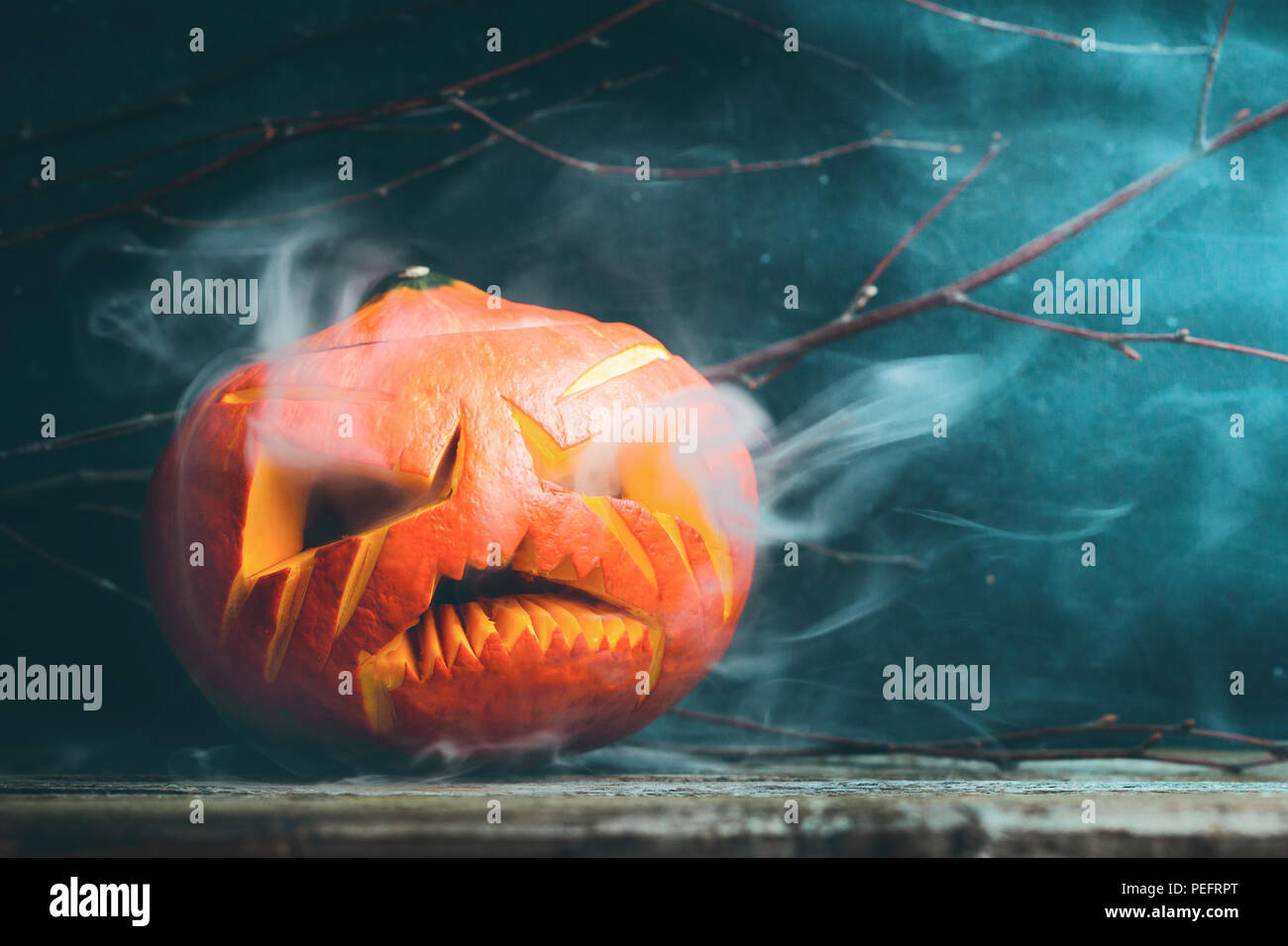Smoky and scary Jack O Lantern head pumpkin still life. The concept of Halloween. Place for text. Stock Photo