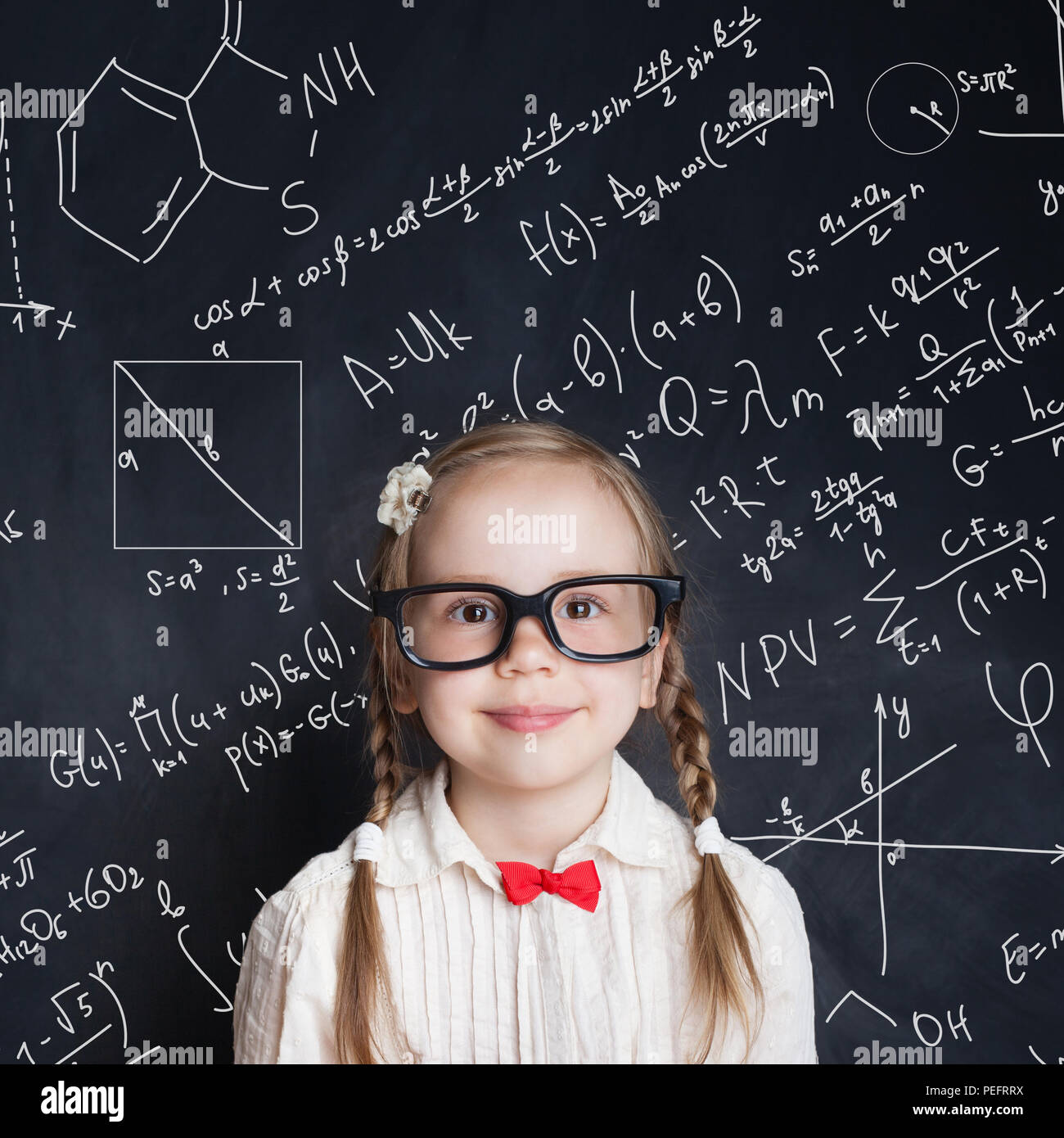 Little genius. Smart little girl math student on school blackboard background with hand drawings science formula pattern. Kids mathematics education c - Stock Image