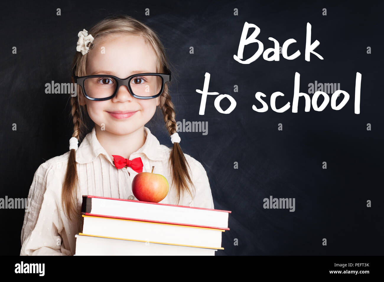 f7b6c9177a85 Smiling child girl in school uniform holding books and apple against chalk  board background. Back to school concept