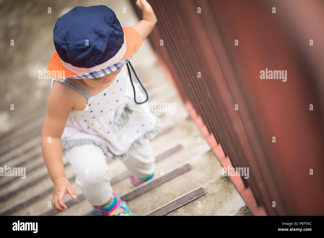 Happy Little Cute Girl Walking Up The Stairs. Kid First Step Concept.