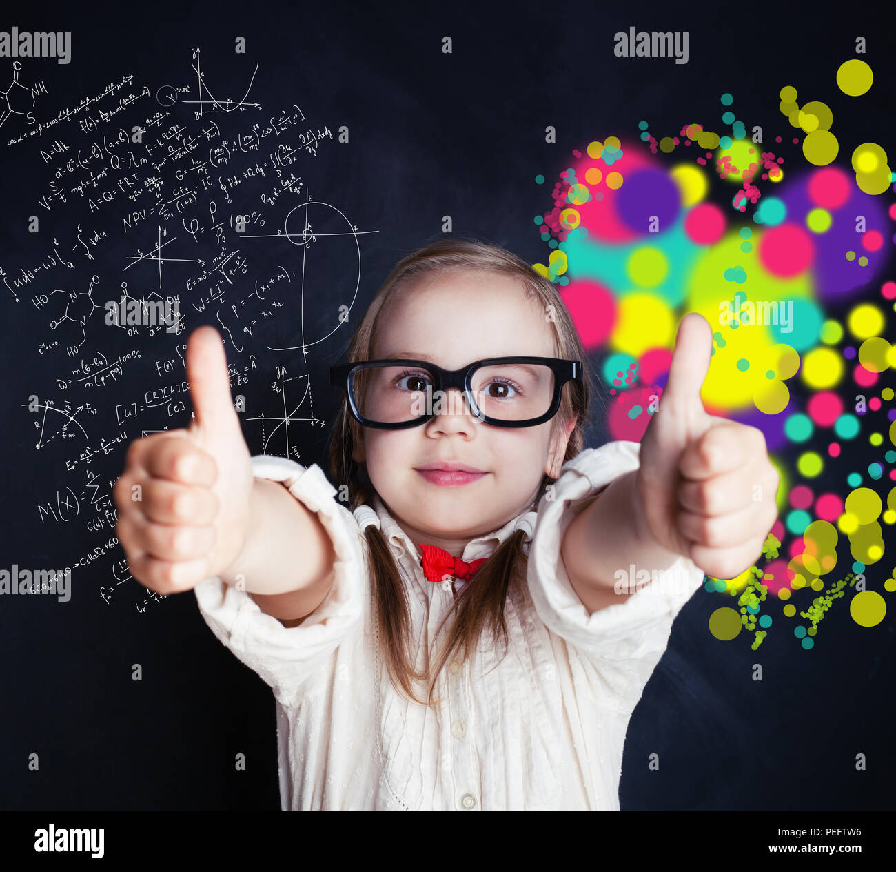 Little genius girl on chalk board in classroom with symbol of right and left hemispheres of the brain - science and arts elements - Stock Image