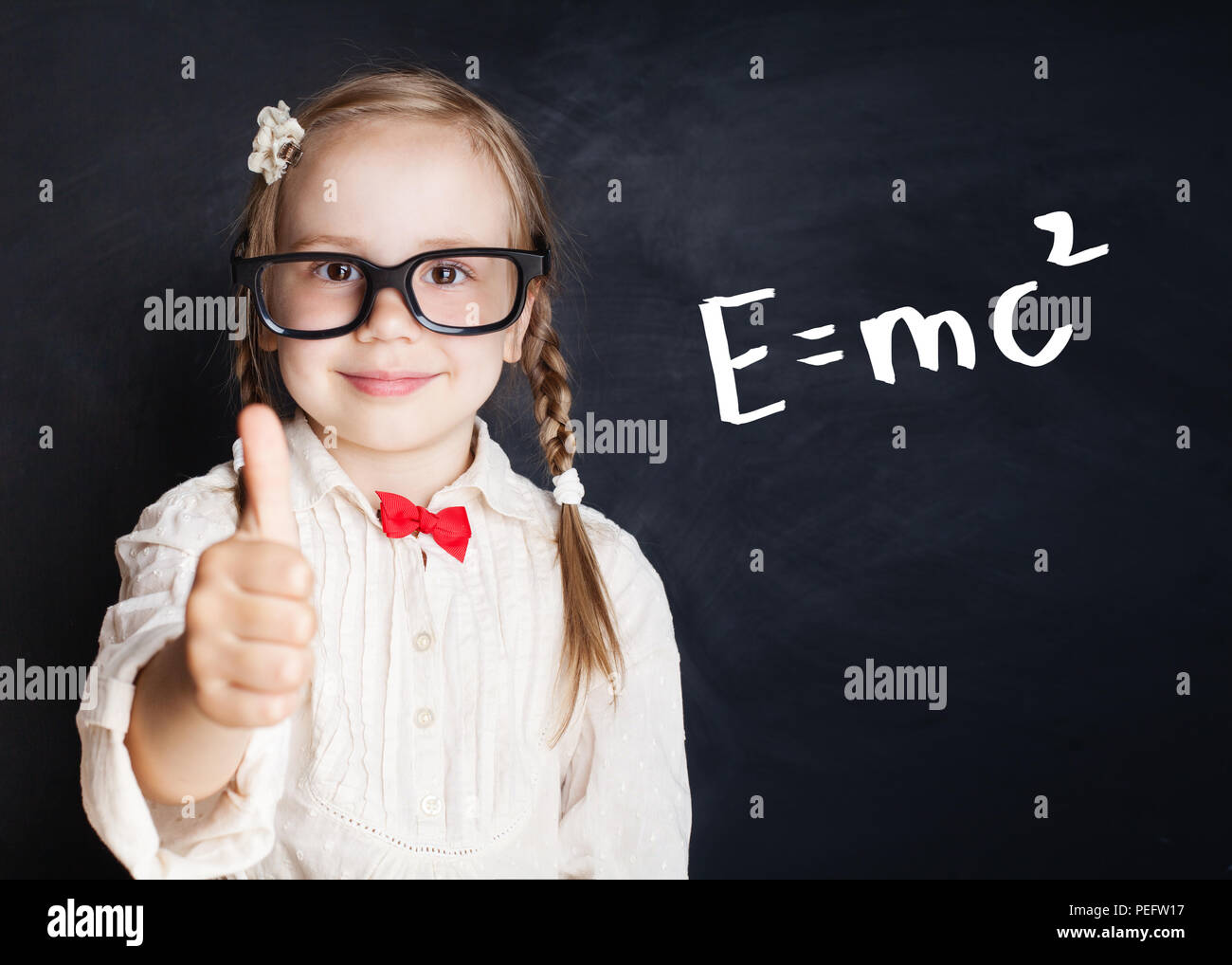 Little genius portrait. Kids mathematics education concept. Little girl with thumb up on hand drawings math science formula pattern - Stock Image