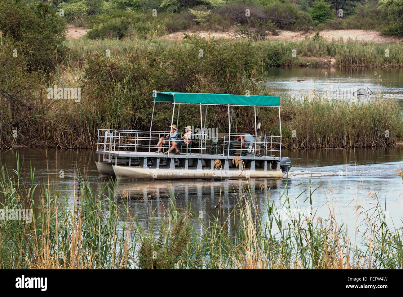 tourist boat on the okavango river in namibia. - Stock Image
